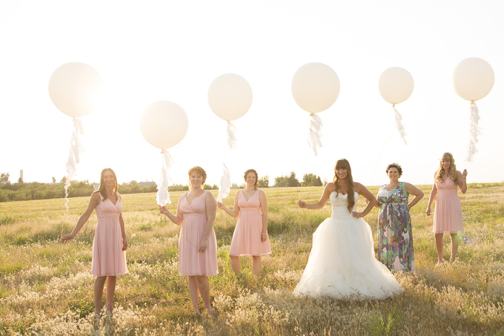 bridesmaids pose with large white balloons in a field