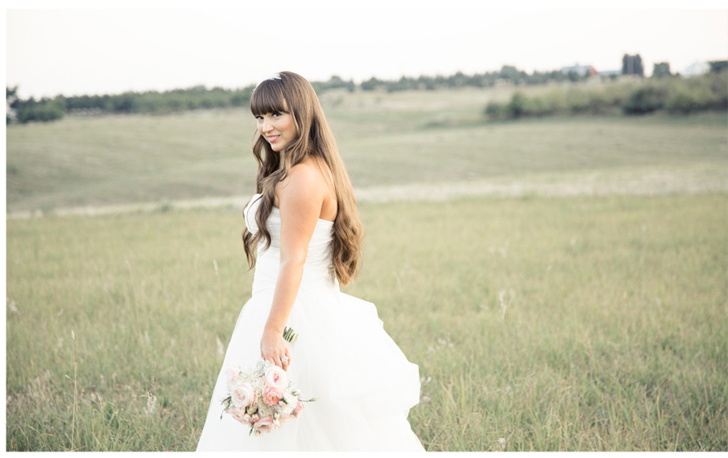 bride poses alone in field with bouquet