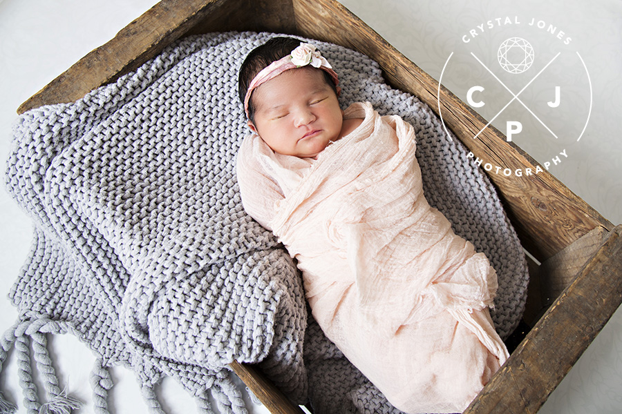 Sleepy newborn baby girl in vintage crate