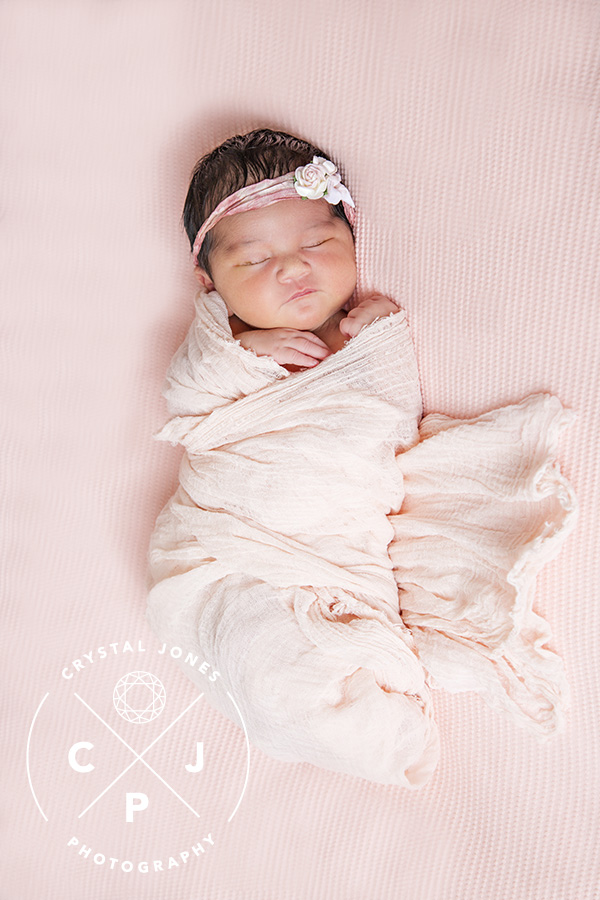 Sleepy newborn baby girl in light pink