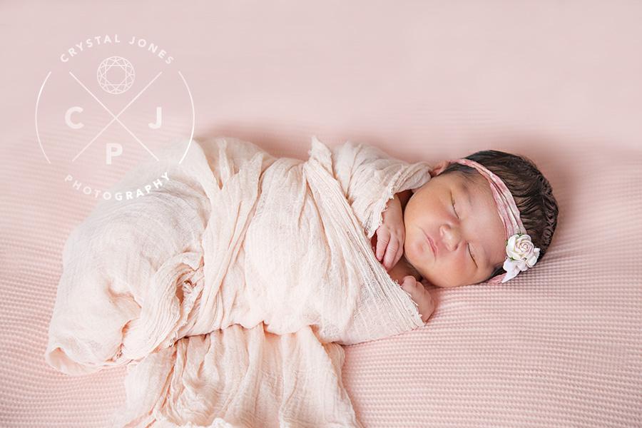 Sleepy newborn baby girl in light pink