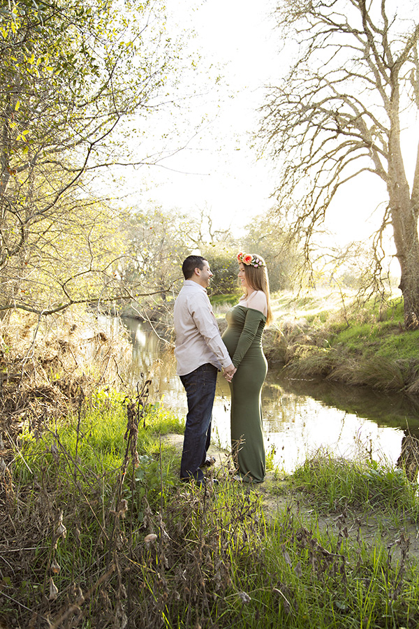 Sunset couples maternity photos in front of a creek